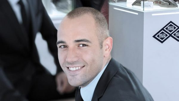 Smiling young businessman with dark suit in meeting